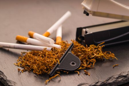 cigarette machine with tobacco and cigarettes on a black background