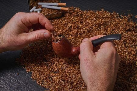 man stuffs a pipe with tobacco, hands closeup