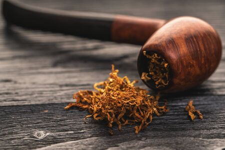 smoking pipe with tobacco on a black wooden background