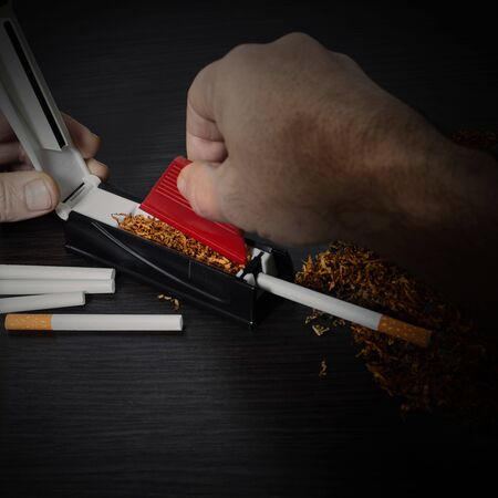 man makes a cigarette with rolling machine, hands closeup