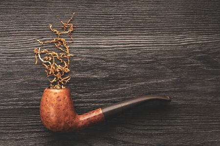 smoking pipe with tobacco on a black wooden background 版權商用圖片