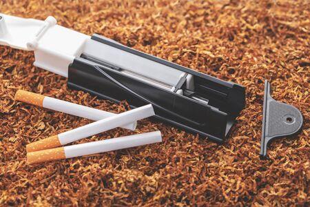 cigarette machine and cigarettes on tobacco background 版權商用圖片