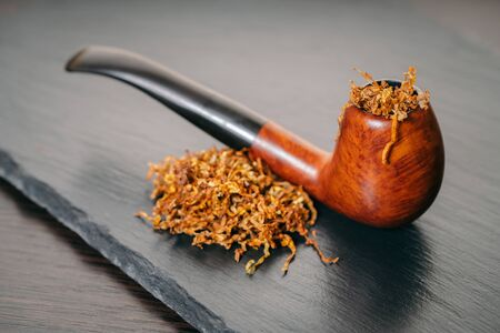 smoking pipe with tobacco on a black background
