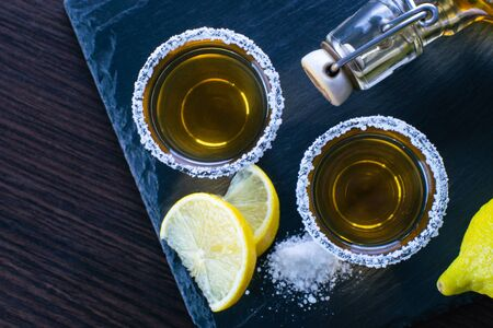 alcoholic drink with lemon and salt on wooden background