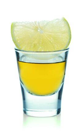 glass with strong alcoholic drink and lemon on a white isolated background