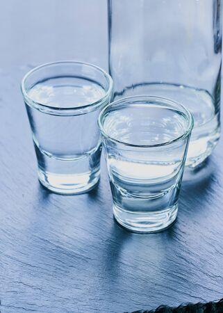 bottle of vodka and glasses of alcohol on a dark background Standard-Bild
