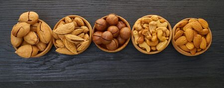 set of nuts in a bowl on black wooden background
