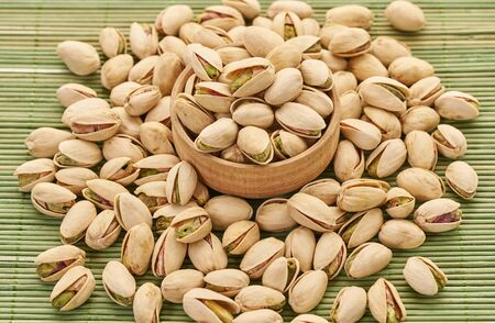 fresh pistachios close-up on a green wooden background