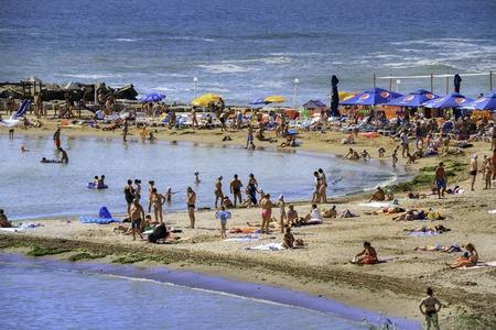 neptun: Unidentified people enjoying the sun on a beach at Jupiter sea summer resort on 30 Iuly, 2014, Romania