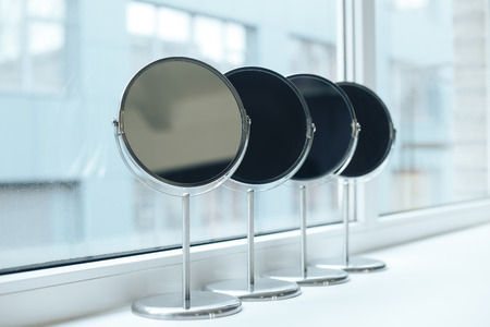 four silver makeup mirror are hardly near the window Stock Photo
