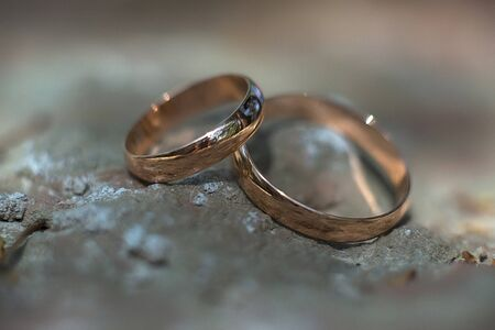 weddingrings: two golden wedding rings on the stone, wedding rings background concept