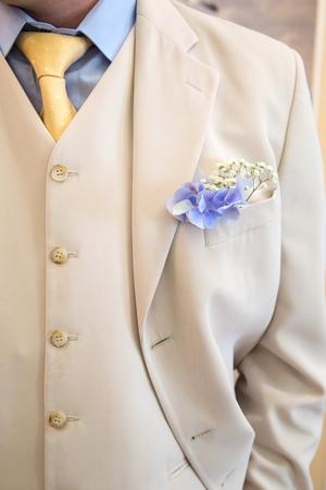 buttonhole flower on grooms wedding coat. detail of grooms wedding dressup