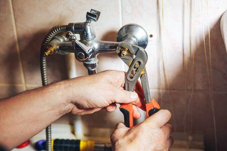 to mend: Man repair and fixing leaky faucet in bathroom