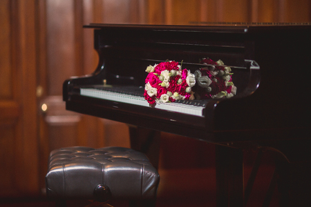 beautiful modern wedding bouquet on a black piano on the keys? Romantic photo of the wedding day
