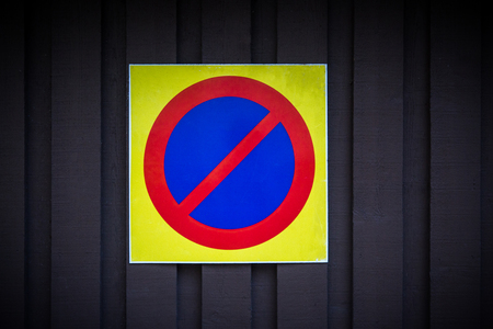 forbid: No parking sign. Prohibition symbol. Sign indicating warning and forbidden. Grunge shabby paper sticker isolated on dark wooden background.
