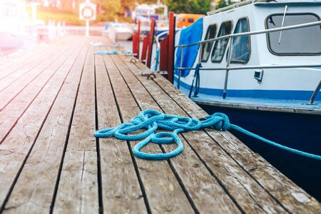 A blue yacht moored with a line tied around a fixing on the quayside Mooring at a pier Stock Photo