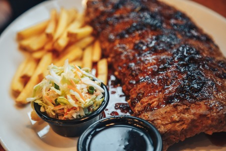 Close up Gourmet Grilled Pork Rib and Fried Potato Wedges on wood Plate with Sauce Foto de archivo
