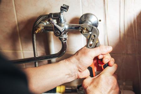 Man repair and fixing leaky faucet in bathroom