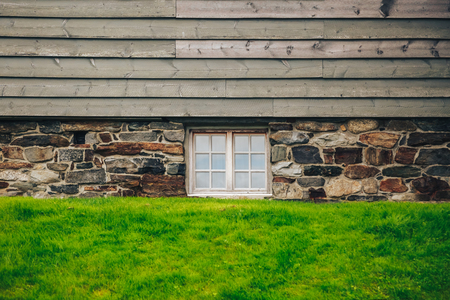 louver: a wall of a stone house with a wooden roof on green grass. abstract background, roof, house with window and grass located on the same plane parallel lines