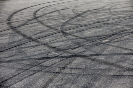 Abstract transportation background with turning black tire tracks over dark asphalt road pavement 写真素材