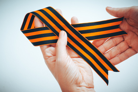 orange and black striped ribbon symbol on May 9 in hands. the symbol of the great Victory over the Nazis, victory day,