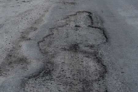 Broken city asphalt road with a lot of pits. Depressive urban landscape. Stock Photo