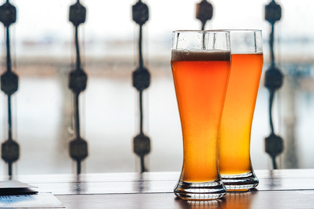 Two glasses of beer on a bar table. Beer Tap on background Stock Photo