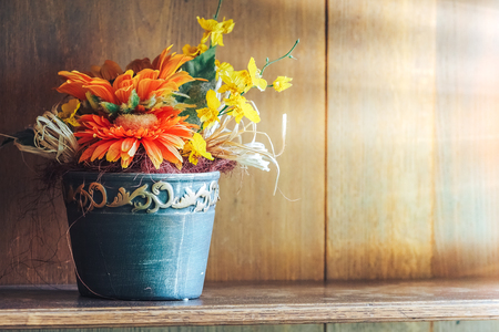 Artificial multi-colored flowers on the shelf in the closet, as the decor of the house and comfort, with sunlight Archivio Fotografico