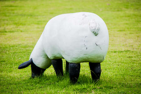 The model is made of cement, white sheep standing in the middle of the lawn.