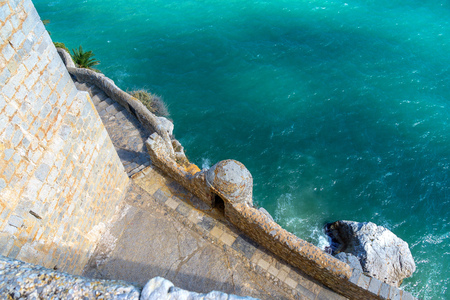 Stone wall and sea in Spain. A small path between the imposing city wall and the Mediterranean Sea.