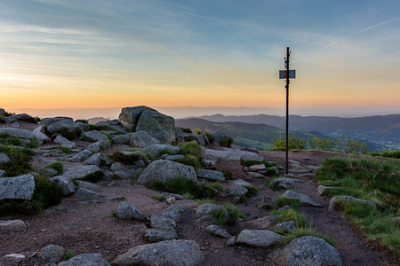French countryside - Vosges. Hiking trail at sunrise with a signpost and a breathtaking view of the Rhine valley and the Black Forest in the background. Stock Photo