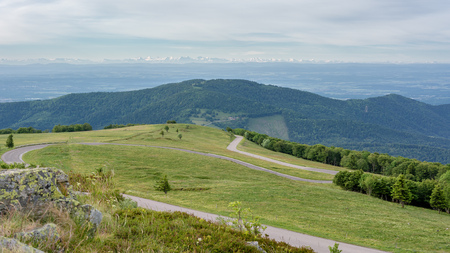 French countryside - Vosges. Panoramic view to a valley in the Vosges and a road through the mountains. In the background you can admire the Alps.