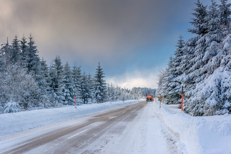 Wintertime - Black Forest. Winter landscape with snowplow clearing road after snowstorm.