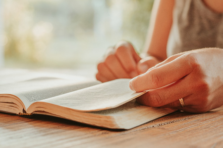 Christian worship and praise. Hands of a young woman on an open Bible in the early morning Stockfoto