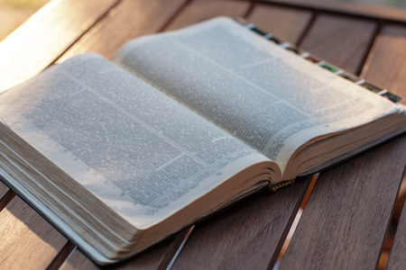 Christian worship and praise. The open bible on a chair in the morning light. Stock Photo