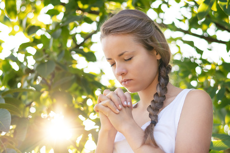Christian worship and praise. A young woman is praying in the early morning with sun in the background.