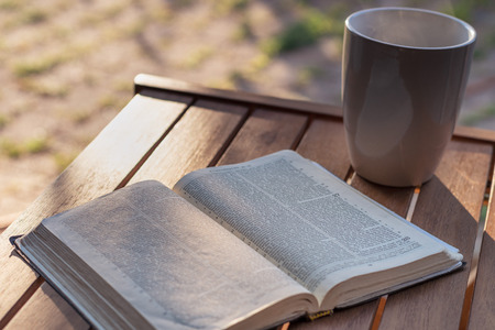 Christian worship and praise. The open bible on a chair in the morning light with cup of coffee.