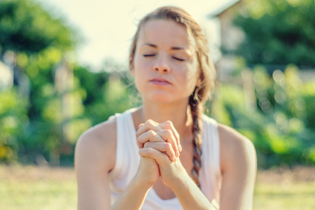 Christian worship and praise. A young woman is praying in the early morning.