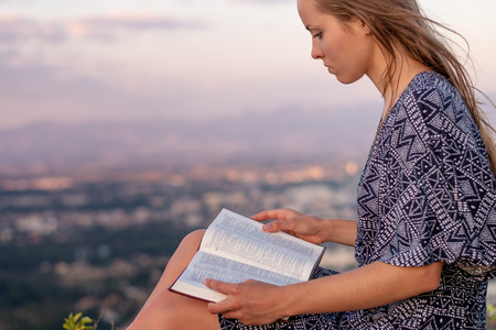 Christian worship and praise. A young woman is reading the bible. Stok Fotoğraf