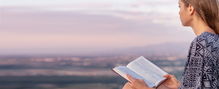 Christian worship and praise. A young woman is reading the bible. 免版税图像