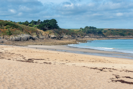 French landscape - Bretagne. Beautiful sandy beach with rocks in the background.
