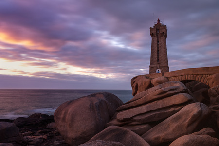 French landscape - Bretagne. View over the famous pink granite coast and the lighthouse Men Ruz at sunset.