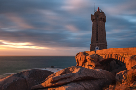 French landscape - lighthouse II. View over the famous pink granite coast and the lighthouse Men Ruz at sunset. Reklamní fotografie - 115840462