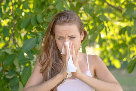 Summertime in garden. Young woman is cleaning her nose due to pollen allergy.