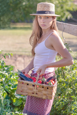 Summertime in garden. Young beautiful woman holding basket full of freshly harvested vegetables in her garden. Homegrown bio produce concept.