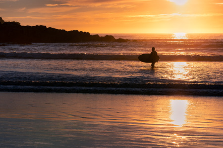 French landscape - Bretagne. Beautiful rocky and sandy beach with view over the sea and surfer.
