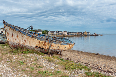 French landscape - Bretagne. Old wooden boat on the peninsula of Crozon with harbor in the background.