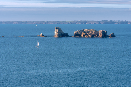 French landscape - Bretagne. Beautiful rocky coast with sailboat and view over the sea.