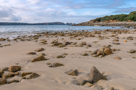 French landscape - Bretagne. A beautiful beach with boat and wild cliffs in the background.