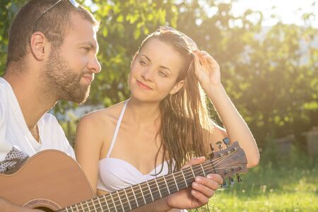 Summertime in garden. Young couple is playing acoustic guitar in the garden at sunset. Stock Photo